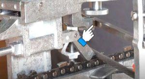 Ролик с поперечиной на станке для заточки цепи