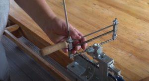 Закрепить напильник в конструкции станка для заточки цепи